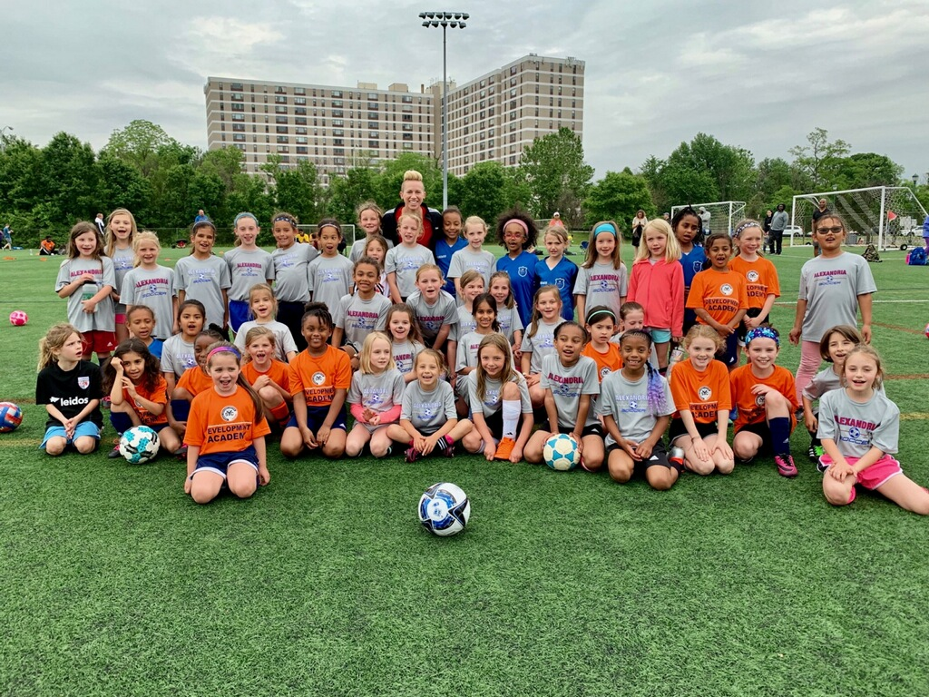 Junior Academy girls pose with Joanna Lohman after practice
